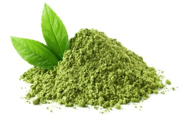 Heap of green tea leaves and powder